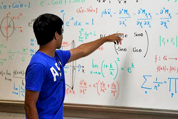 Young Man in Front of Board filled with Equations